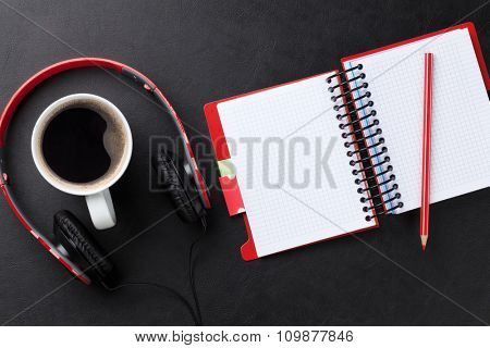 Office leather desk with notepad, coffee cup and headphones. Top view with copy space