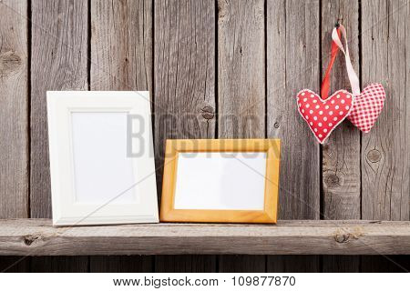 Two photo frames and Valentines day hearts on rustic wooden wall with copy space
