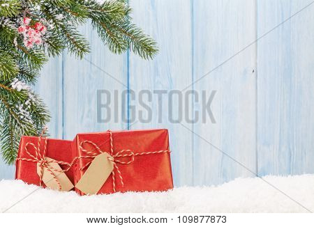 Christmas gift boxes and fir tree branch in snow. View with copy space