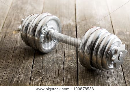 iron dumbbell on old wooden background