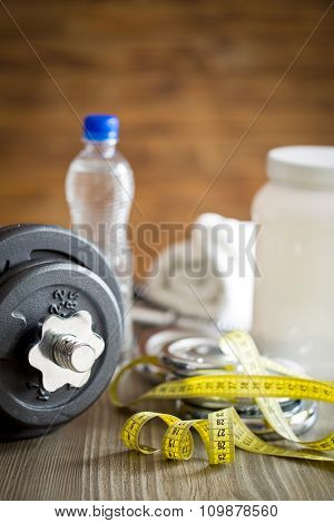 measuring tape and iron dumbbell on wooden floor