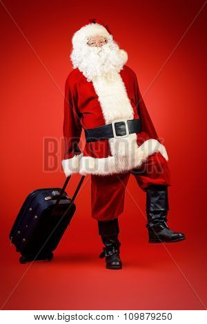 Santa Claus walking with a modern suitcase over red background. Christmas time. Christmas tours.
