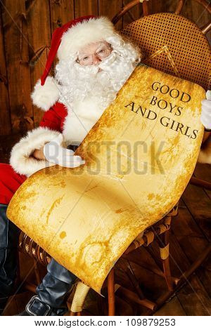Santa Claus sitting in his wooden house in a comfortable chair. He checks his list of good boys and girls. Christmas time.