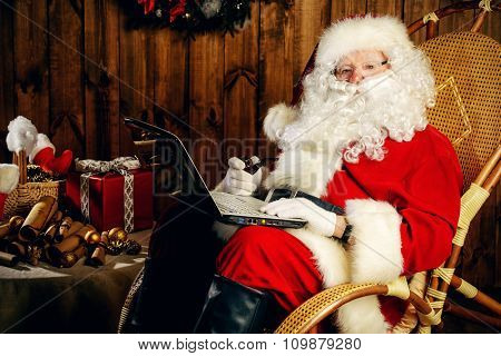 Modern Santa Claus at his wooden house working on his laptop and smoking a pipe. Christmas.