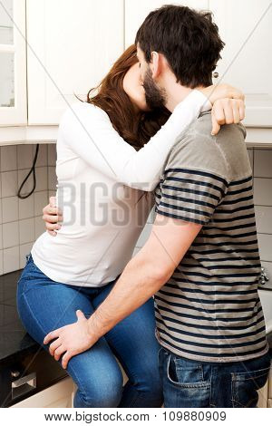 Young beautiful couple kissing in the kitchen.