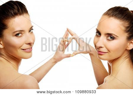 Two beautiful women making heart with fingers.