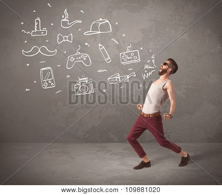 A funny hipster person in casual urban clothing shouting drawn everyday items like camera, tie or pen on city wall concept
