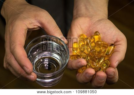 Hands Hold Pills And Glass Of Water