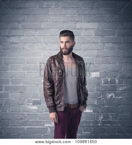 A stylish hipster guy with beard and sunglasses standing in casual clothes in front of an urban blue brick wall background concept