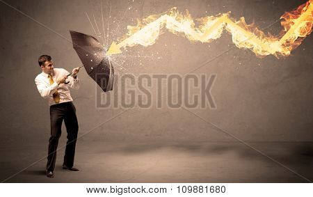 Business man defending himself from a fire arrow with an umbrella on grungy background
