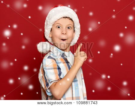 boy in santa helper hat show finger on red background with snow