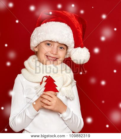 girl in santa hat portrait with fir tree wool toy on red  with snow
