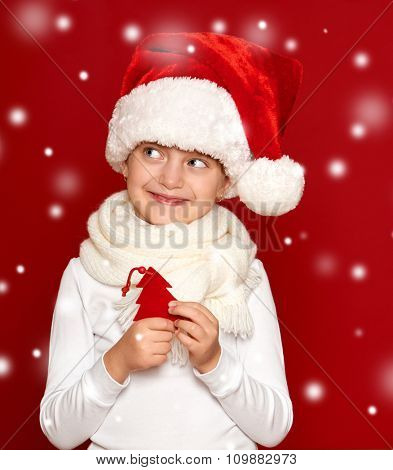 winter, child,  christmas concept - happy girl in santa hat show fir tree wool toy on red background
