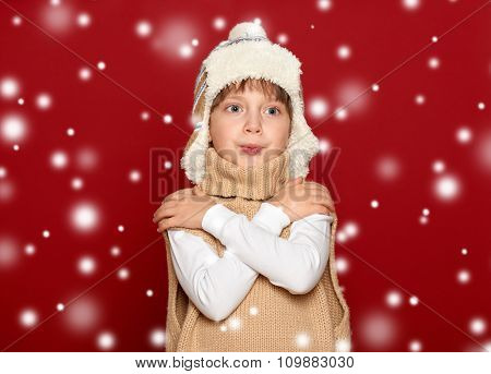 winter, people, happiness concept - girl in hat and sweater on red background