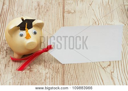A Golden Piggy Bank With Grad Cap And Gift Tag On Wood Background