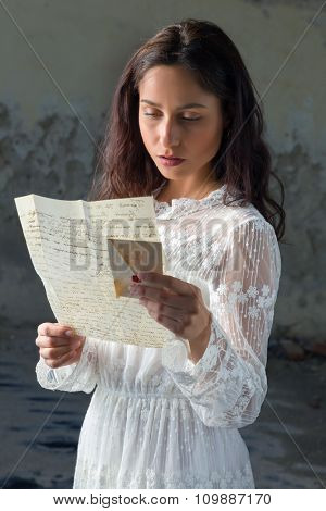 Young woman in antique lace dress reading a sad letter