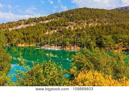 Mountain canyon Verdon in the French Alps. Smooth emerald river water reflects the sky and wooded shore