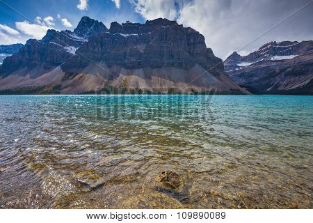 Azure Bow Lake in Banff National Park. The cold waters of the lake surrounded by scenic Canadian Rocky Mountains
