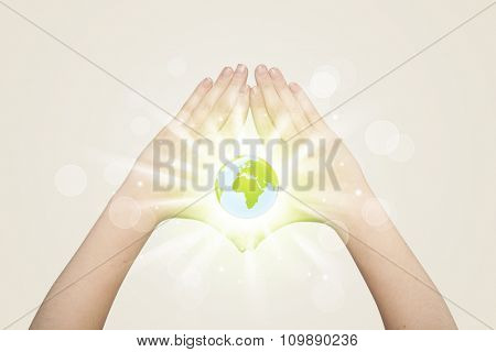 Hands creating a form with shining globe in the centera