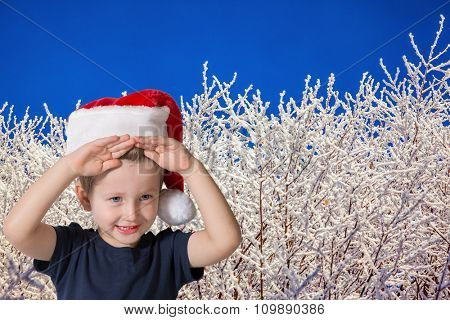 Three year old boy in red cap of Santa Claus. Cute kid having fun smiling on the background of snow-covered forest