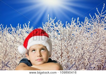 Very beautiful seven year old boy in red hat of Santa-Claus smiling  on the background of the winter forest