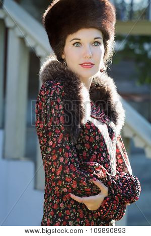 Cheerful Russian beauty in traditional fur Cossack hat and crossed hands