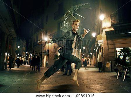 Sporty businessman running with an umbrella