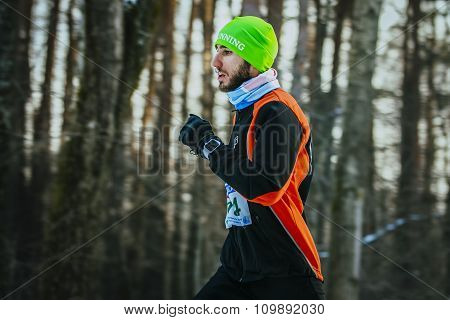 young male runner running through forest
