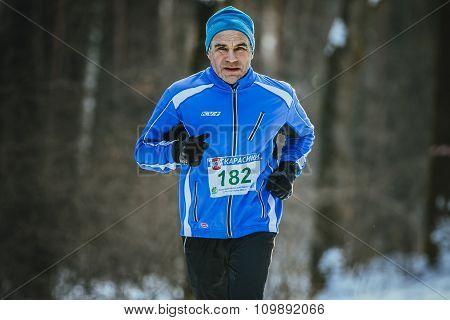 old men athlete runs at winter Park