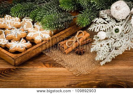Christmas cookies with cinnamon and anise on the tray on the wooden background.