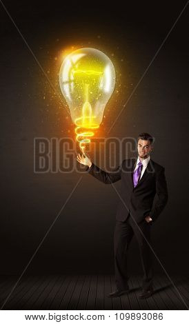 Businessman holding a shining idea bulb