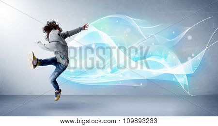 Cute teenager jumping with abstract blue scarf around her concept on background