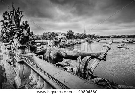 Artistic statue on Pont Alexandre III bridge in Paris, France. Seine river and Eiffel Tower. Black and white