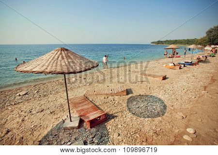 Beach On Turkish Resort Sun Umbrellas And People Swimming In Calm Sea Waters