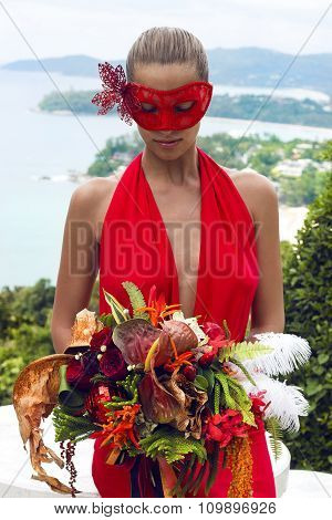 Beautiful woman in carnival mask with bouquet flowers wearing red dress poses on tropical sea view.