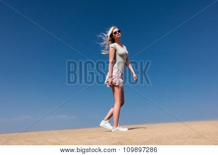 A young girl wearing a skirt posing on the sand