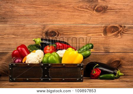 Fresh vegetables in the wooden box on the rustic background.