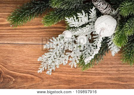 Christmas decoration - silver and green coniferous branches on the wooden background.