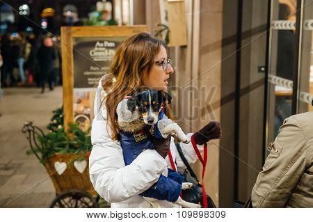 Christmas Market With Tourist Holding  Dressed Dog