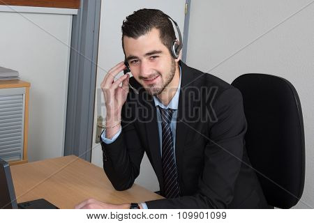 Call Centre Operator Or Client Services Businessman Wearing A Headset Looking Up Information In A Fi