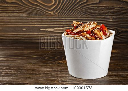 Delicious Wok Noodles Box Container With Udon And Chicken On Wooden Table. Chinese And Asian Takeawa