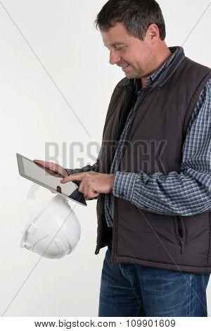 Cheerful Worker In White Helmet Holding Shockproof Digital Tablet In Both Hands.