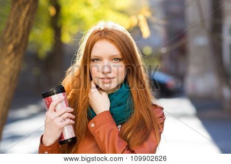Attractive redhead young female with long hair in leather jacket and scarf drinking tea in the park in autumn