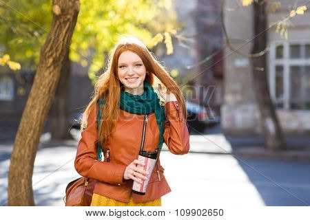 Smiling  positive pretty young woman with beautiful long red hair in leather jacket and scarf holding tumbler of coffee and walking in the street