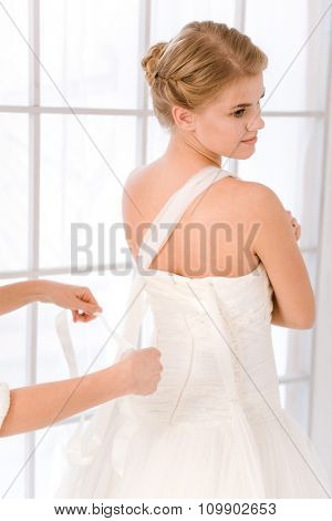 Beautiful bride putting on her white wedding dress