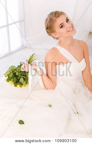 Portrait of a smiling bride holding wedding flowers and looking at camera