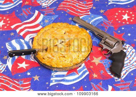 Apple pie with a handgun on an American flag background symbols of Americana