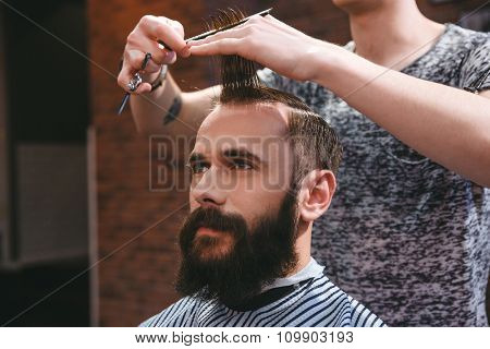 Portrait of young handsome man with beard having a haircut with comb and scissors in hair salon