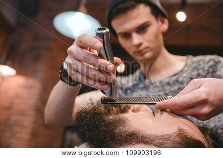 Young concentrated skillful barber making perfect beard to handsome bearded man using trimmer and comb in hair salon
