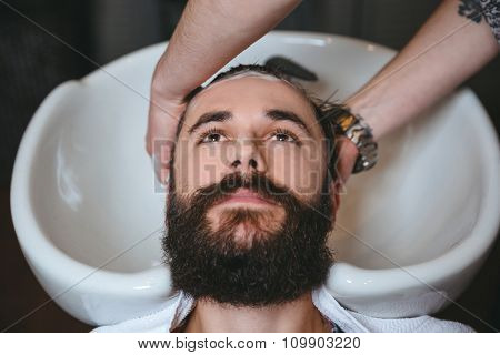 Hairstylist washing head of young attractive man with beard in barbershop